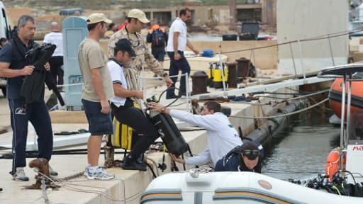 Les plongeurs des pompiers préparent leur équipement pour reprendre les recherches, dimanche, dans le port de Lampedusa.