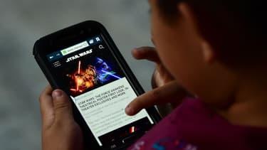 Un enfant lit un article sur un téléphone portable, le 20 octobre 2015 à Los Angeles (Etats-Unis)