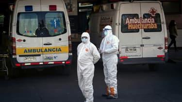 Des personnels soignants attendent près d'une ambulance transportant une personne atteinte par le coronavirus, le 5 juin 2020 à Santiago du Chili