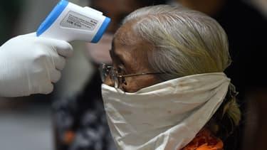 Un médecin prend la température d'une femme à Mumbai (Inde), le 10 juillet 2020.