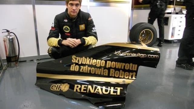 Vitaly Petrov pose devant l'aileron qui rend hommage à Robert Kubica