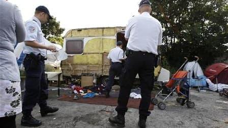 """Policiers effectuant un recensement dans un camp illégal de Roms à Saint-André-lez-Lille, dans le Nord. """"La France ne s'en prend pas aux Roms"""", estime le ministre de l'Immigration Eric Besson, qui s'indigne des attaques de l'opposition et de certains élus"""