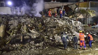 Des secouristes à la recherche de survivants dans les décombres d'un bâtiment effondré