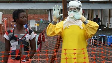 Un médecin communique par gestes alors qu'il se trouve dans la zone confinée à haut-risque à côté d'une patiente, le 7 septembre 2017 à Monrovia, capitale du Libéria.