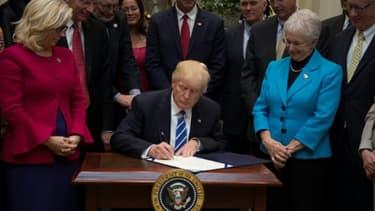 Le président américain Donald Trump signe des décrets à la Maison Blanche, le 27 mars 2017 à Washington