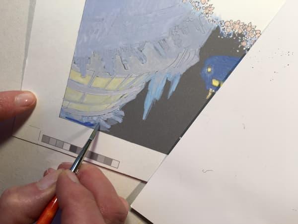 Evelyne Tranlé en train de colorier une planche.