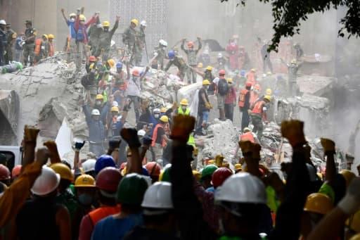 Des sauveteurs font le signal du silence durant des recherches de survivants dans un immeuble effondré à Mexico, le 21 septembre 2017, deux jours après un puissant séisme qui a fait au moins 240 morts.