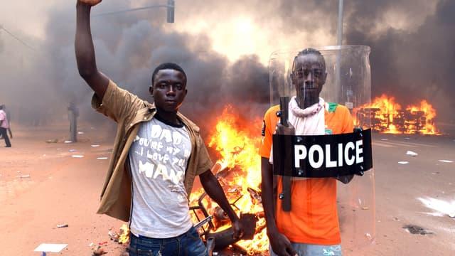 De jeunes Burkinabè devant le Parlement incendié, jeudi 29 octobre, à Ouagadougou.