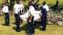 Policiers et gendarmes transportant le débris, qui semble être un morceau d'aile.
