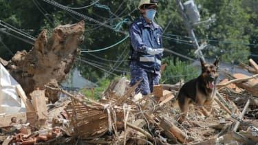 Un sauveteur et son chien à la recherche de disparus dans les décombres à Kure, dans la préfecture d'Hiroshima , le 12 juillet 2018