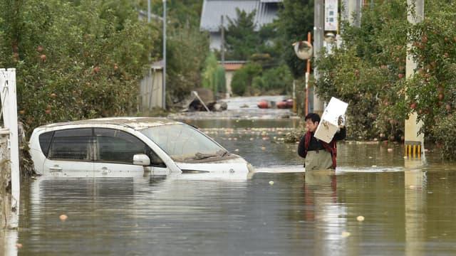 Un homme dans une rue inondée de Nagano, au Japon, le 14 octobre 2019