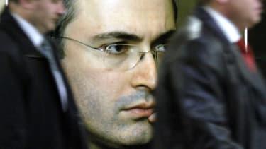Deux hommes passent devant une photo de Mikhaïl Khodorkovski, en octobre 2003, au siège moscovite de la compagnie Youkos..