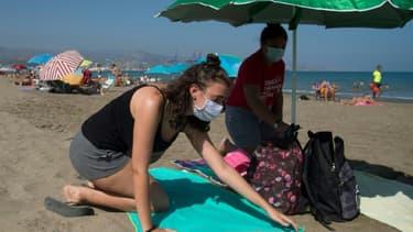 Masqués les vacanciers se préparent à s'installer sur la plage à Malaga, le 22 juillet 2020. (illustration)