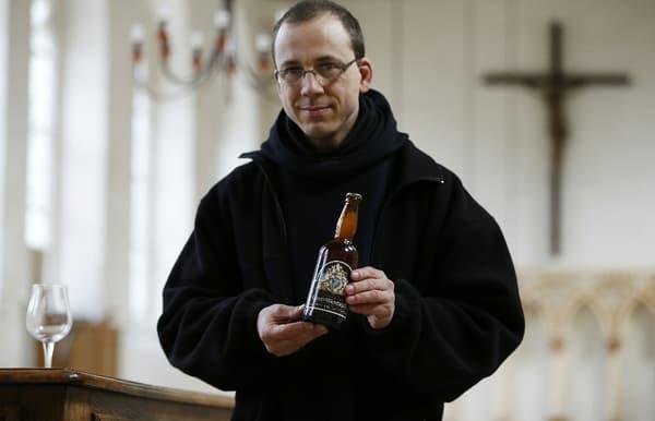 Le Frère Benoît pose avec une bouteille de bière de l'abbaye Saint-Wandrille.