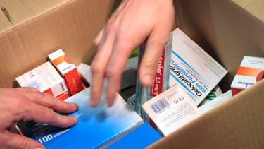 Caisse contenant des boîtes de médicaments. (Illustration)