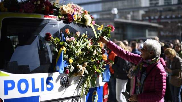 Une femme dépose des fleurs sur une voiture de la police suédoise à Stockholm dimanche 9 avril