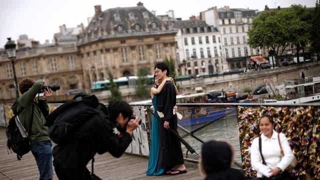 Des touristes se font photographier devant le Pont des Arts. Une partie de la rambarde a déjà été remplacée par du plexiglas.