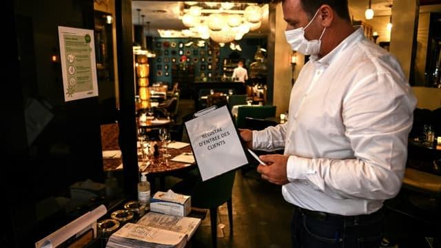 """Les clients des restaurants devront laisser leur nom, leur numéro de téléphone et éventuellement leur adresse mail dans un """"cahier de contact"""", comme ici à Paris le 5 octobre 2020. Ils pourront ainsi être prévenus par l'Assurance maladie en cas de détection d'un cas de Covid-19 chez un consommateur venu dans l'établissement"""