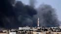 Fumée noire au-dessus du quartier de Salaheddine, considéré comme une porte d'entrée dans Alep pour l'armée syrienne. Les forces de Bachar al-Assad tentent d'enfoncer cette ligne de front rebelle. /Photo prise le 4 août 2012/REUTERS/Goran Tomasevic