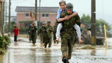 Des militaires japonais aident la population à évacuer, le 6 juillet 2017 à Asakura