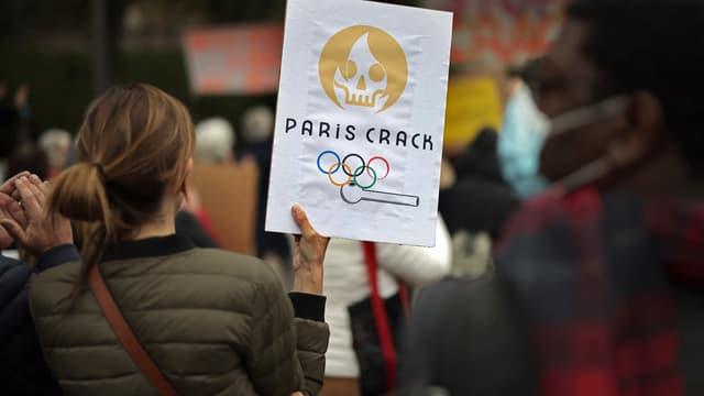 Une manifestante tient une pancarte montrant une caricature du futur logo des Jeux olympiques de Paris 2024, alors qu'elle participe à une manifestation contre l'insécurité liée au crack à Paris, le 2 octobre 2021.