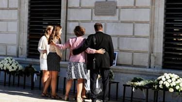 Les proches des victimes se recueillent devant la plaque commémorative dévoilée lundi.