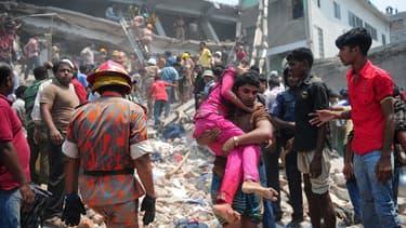 Des civils prêtant main forte à des secouristes pour tenter de retrouver des survivants après l'effondrement d'un immeuble près de Dacca.