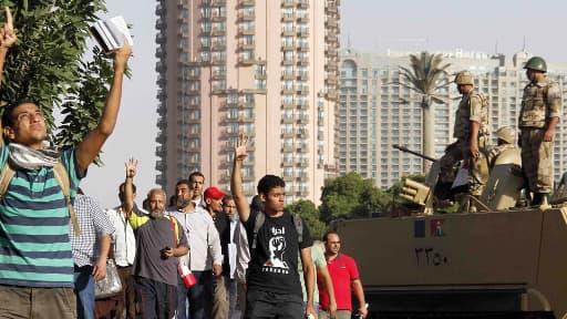 Au Caire, des manifestants pro-Morsi ont défilé, quatre doigts dressés,  un geste devenu le symbole de la répression à Rabaa al-Adawiya.
