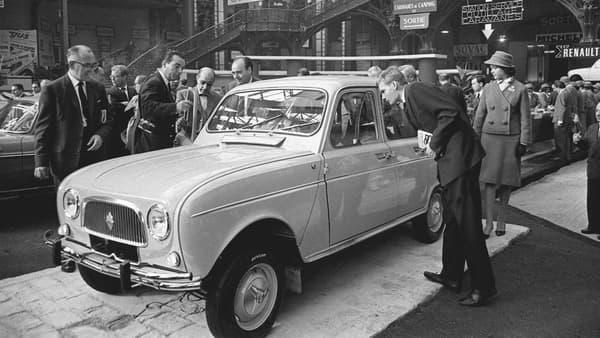 Des visiteurs observent la nouvelle 4L, présentée par Renault le 5 octobre 1961 au salon automobile de Paris, au Grand Palais.