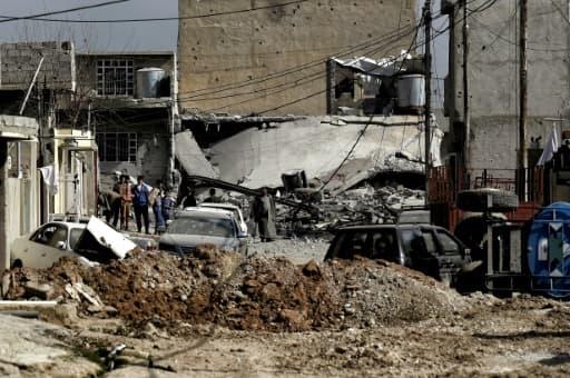 Des habitants au milieu d'un quartier en ruines le 1er mars 2017 à Mossoul