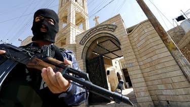 Un officier irakien garde une église catholique aux environs de Bartala, près de Mossoul, le 15 juin.