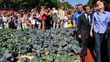 Nicolas Sarkozy et son épouse Carla ont effectué lundi matin une visite surprise à la ferme géante installée par des agriculteurs sur les Champs-Elysées, à Paris. /Photo prise le 24 mai 2010/REUTERS/Philippe Wojazer
