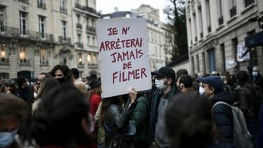 """Un manifestant porte une pancarte """"Je n'arrêterai jamais de filmer"""" lors d'un rassemblement contre la proposition de loi sur la """"sécurité globale"""" à l'appel des syndicats de journalistes et de diverses organisations, à Paris le 17 novembre 2020"""