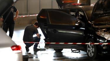 Un officier de la police scientifique examine une voiture abandonnée par Redoine Faïd et ses complices au centre commercial O'Parinor à AUlnay-sous-Bois, le 1er juillet 2018.
