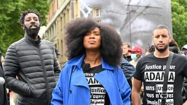 La soeur d'Adama Traoré accompagnée du réalisateur Ladj Ly pose devant un collage de JR en hommage à son frère à Paris, le 9 juin 2020