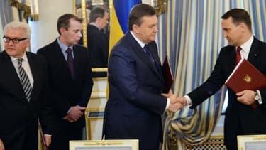 Le président ukrainien Viktor Ianoukovitch (à gauche) et le ministre polonais des affaires étrangères Radoslaw Sikorski (à droite) se serrent la main. .