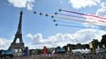 La Tour Eiffel survolée par la Patrouille de France lundi 9 août lors de l'accueil du drapeau olympique au Trocadéro