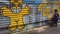 L'artiste peint des chats jaunes sur les murs des villes du monde entier depuis 2007.
