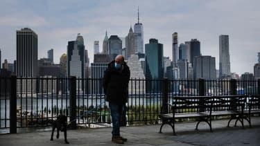 Un homme portant un masque et  promenant son chien à New York le 23 avril 2020