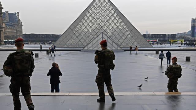 Des soldats de l'opération Sentinelle devant la pyramide du Louvre.
