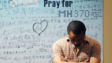 Un homme se tient devant un panneau en soutien aux familles de l'avion disparu de la Malaysia Airlines, à Pékin.