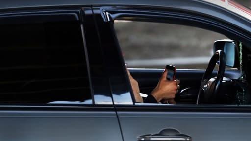 Image d'illustration d'un conducteur avec son téléphone portable à la main