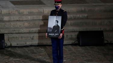 Un garde républicain porte le portrait de l'enseignant assassiné Samuel Paty lors de l'hommage national à la Sorbonne le 21 octobre 2020.