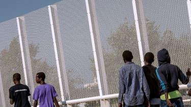 Des migrants marchent à côté d'une clôture bordant la Jungle, à Calais, le 8 septembre 2016.