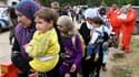 Des membres de la Croix-Rouge libanaise accueillent des civils ayant fui la Syrie à leur arrivée à Wadi Khaled, dans le nord du Liban. Des centaines de Syriens ont fui vers le Liban voisin alors que trois personnes ont trouvé la mort samedi lors de l'entr