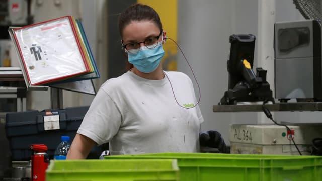 Une salariée de l'usine Valeo travaille avec un masque
