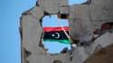 Un drapeau du royaume de Libye, symbole de l'insurrection, à Syrte. Le Conseil national de transition annoncera finalement dimanche à Benghazi la libération du pays. /Photo prise le 21 octobre 2011/REUTERS/Thaier al-Sudani