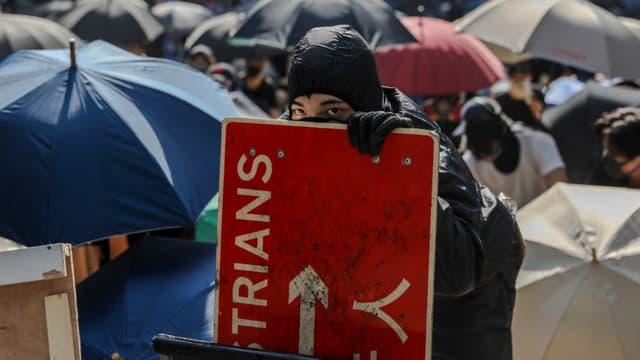Des manifestants et des travailleurs font face à la police pendant une manifestation dans le centre de Hong Kong, le 13 novembre 2019
