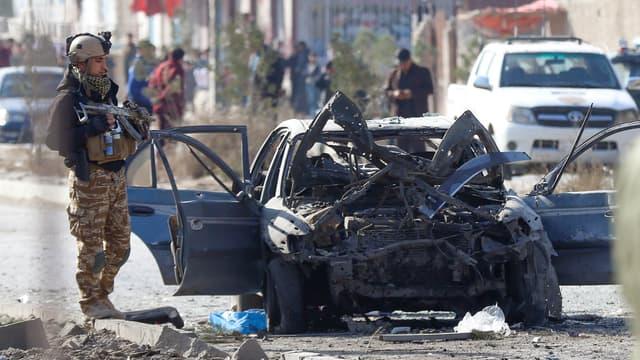Un policier près d'une voiture détruite par une attaque suicide, à Kaboul, le 13 novembre 2019.