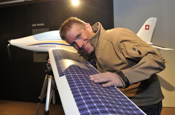L'éco-aventurier suisse Raphaël Domjan posant avec la maquette de l'avion SolarStratos